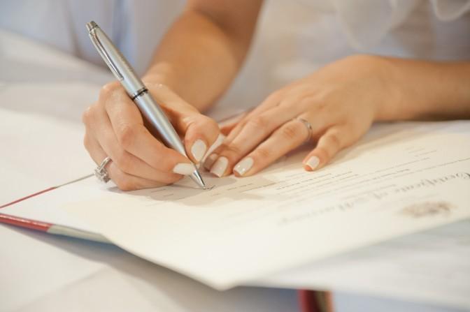 Bride signing wedding certificate